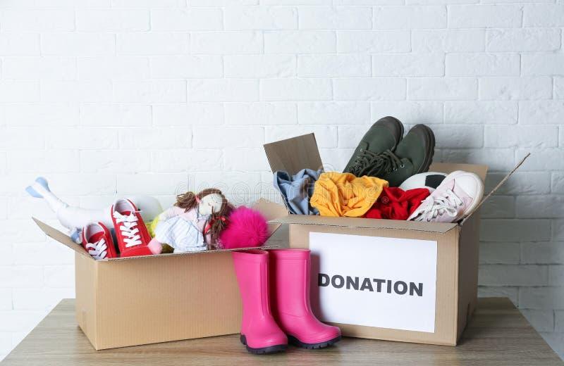 Cajas del cartón con donaciones en la tabla imagen de archivo