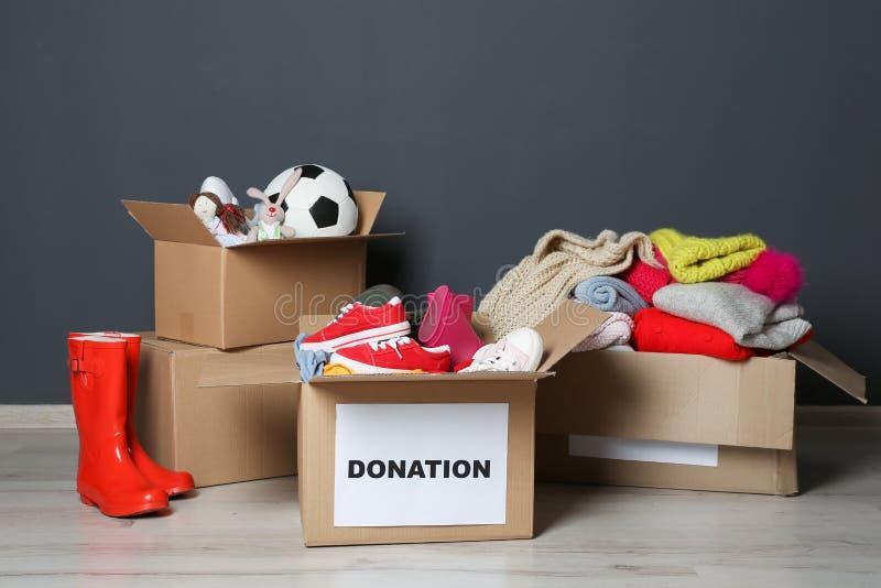 Cajas del cartón con donaciones en piso imagenes de archivo