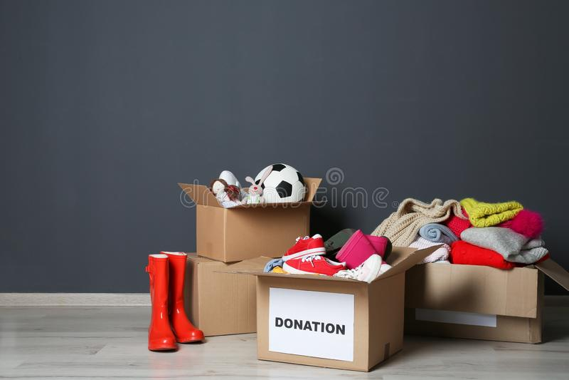 Cajas del cartón con donaciones en piso cerca de la pared gris imágenes de archivo libres de regalías