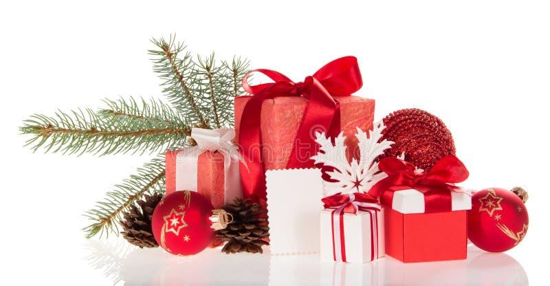Cajas grandes y pequeñas con los regalos, la rama del pino, los conos, los juguetes, y la tarjeta vacía aislada en blanco fotos de archivo