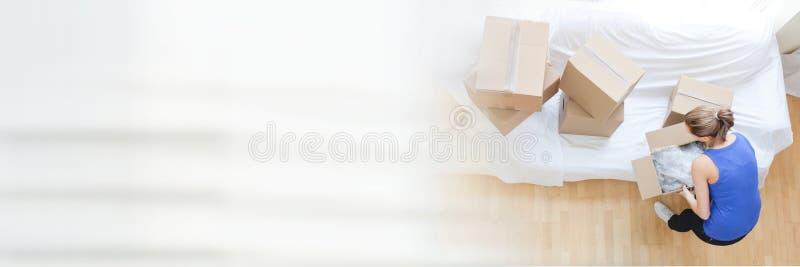 Cajas móviles de la mujer en su nueva casa imagenes de archivo