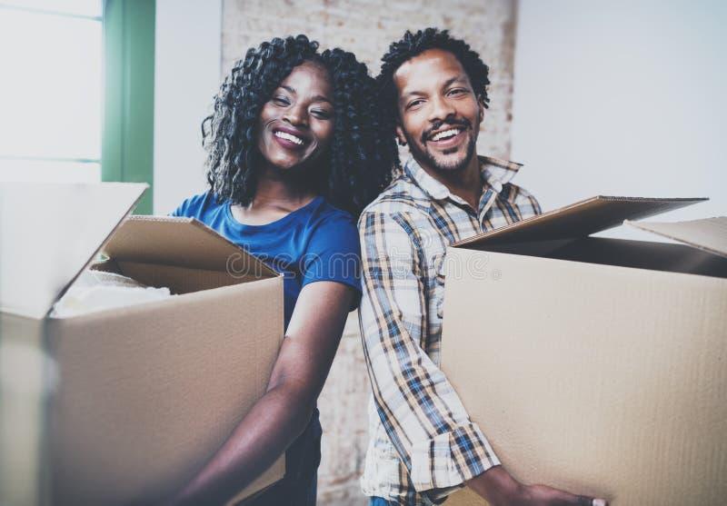 Cajas móviles de los pares jovenes felices del africano negro en nueva casa junto y haciendo una vida acertada Familia alegre foto de archivo libre de regalías