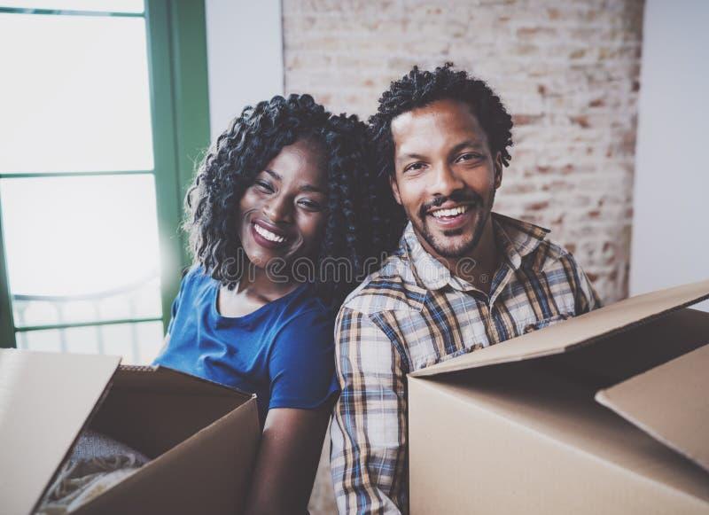Cajas móviles de los pares jovenes felices del africano negro en nuevo hogar junto y haciendo una vida acertada Familia alegre imagenes de archivo