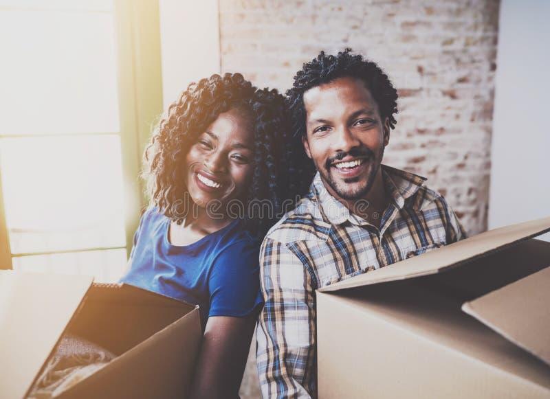 Cajas móviles de los pares jovenes felices del africano negro en nuevo hogar junto y haciendo una vida acertada Familia alegre foto de archivo libre de regalías