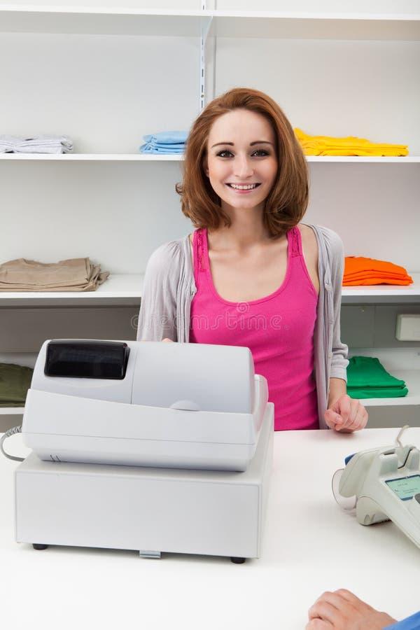 Cajero femenino joven con la caja registradora fotografía de archivo