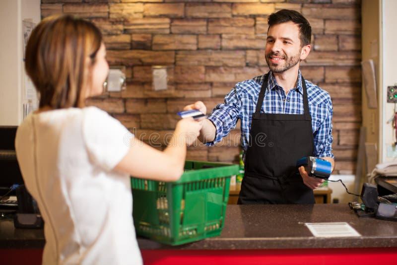 Cajero que recibe un pago con tarjeta de crédito fotos de archivo