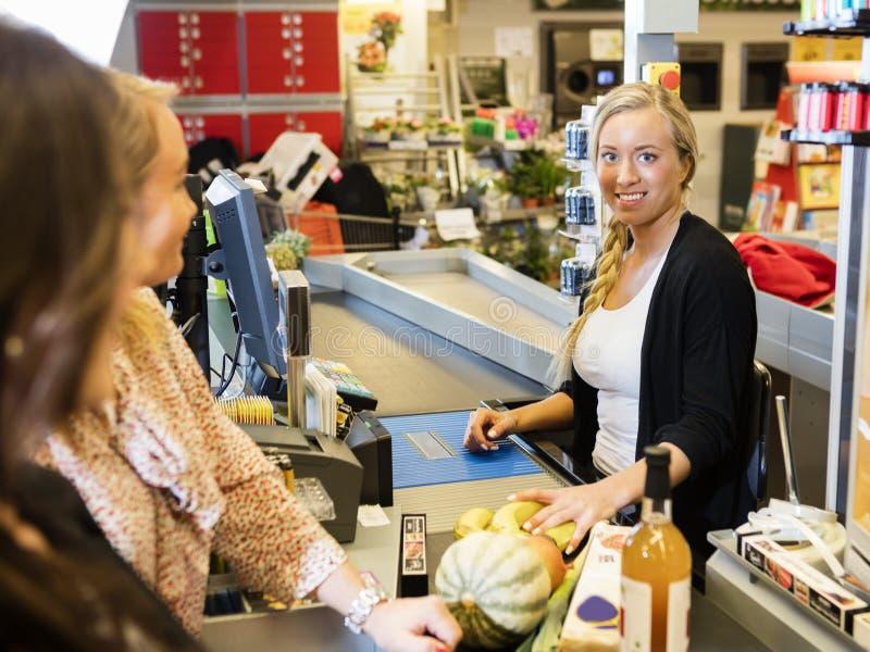 Cajero Smiling While Customers que se coloca en el contador de pago y envío imagen de archivo libre de regalías