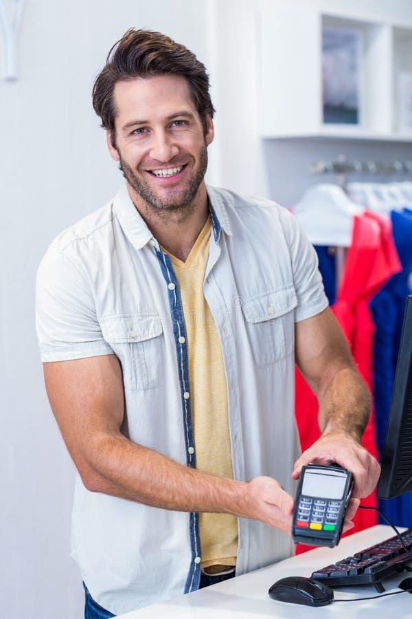 Cajero sonriente que muestra al lector de la tarjeta de crédito imagenes de archivo
