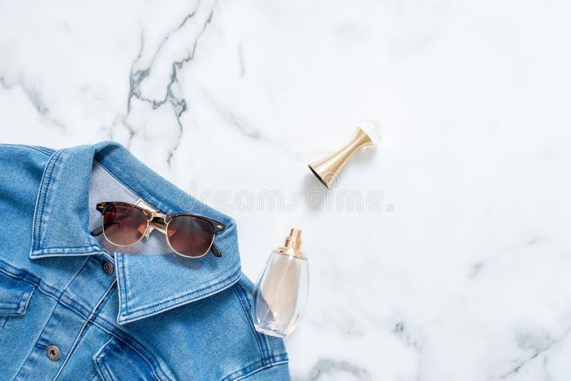 Cajgi kurtka, butelka pachnidło i retro fasonujący okulary przeciwsłoneczni na marmurowym tle, Mieszkanie projekta nieatutowy skł obrazy royalty free