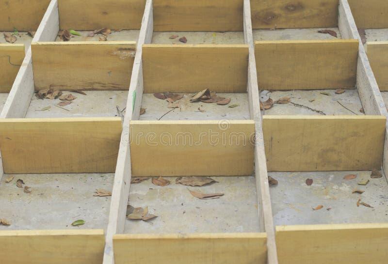 Cajones vacíos en los pisos concretos, encofrado concreto de las hojas secas, caja de madera, caja de madera amarilla, imagenes de archivo