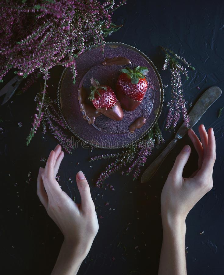 Cake with berries, covered with blue-violet glaze and chocolate with flowers, Cosmic cake, Hand Made pastry with woman hands, Dark. Background stock images