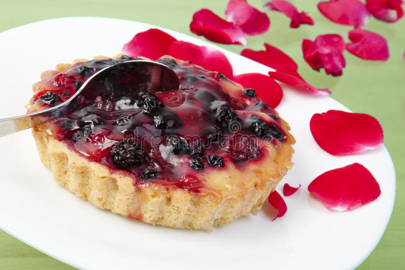 A cake with berries surrounded by roses stock photo