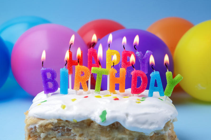Cake with birthday greetings from burning candles on a colored background royalty free stock images
