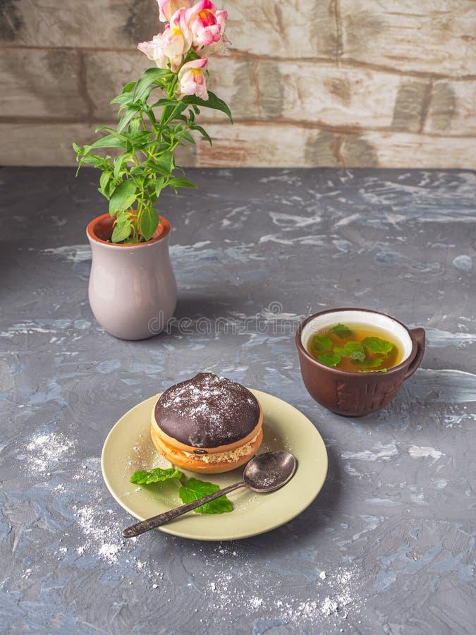 Cake bouche op een kleine plaat met een mok thee en een leeuwebek van de mashinebloem in een kleikop stock foto's