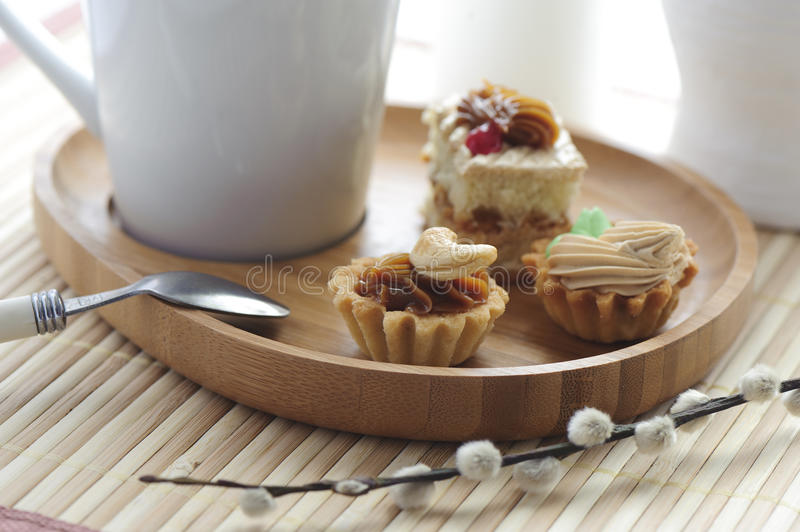 Cake with butter cream and a cup. On a wooden saucer royalty free stock images
