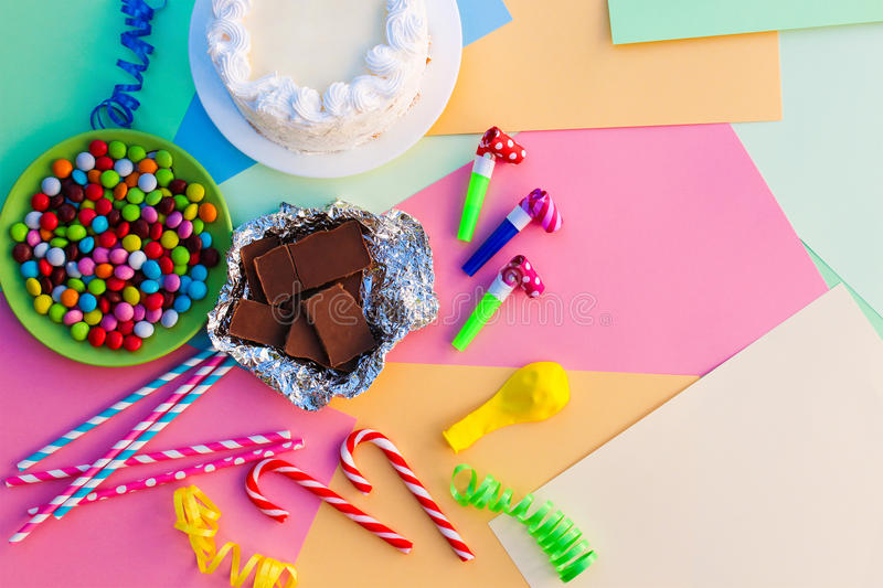 Cake, candy, chocolate, whistles, streamers, balloons on holiday table stock image