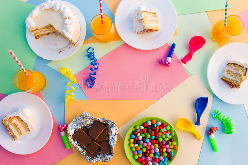 Cake, candy, chocolate, whistles, streamers, balloons, juice on holiday table. Concept of children`s birthday party stock photos