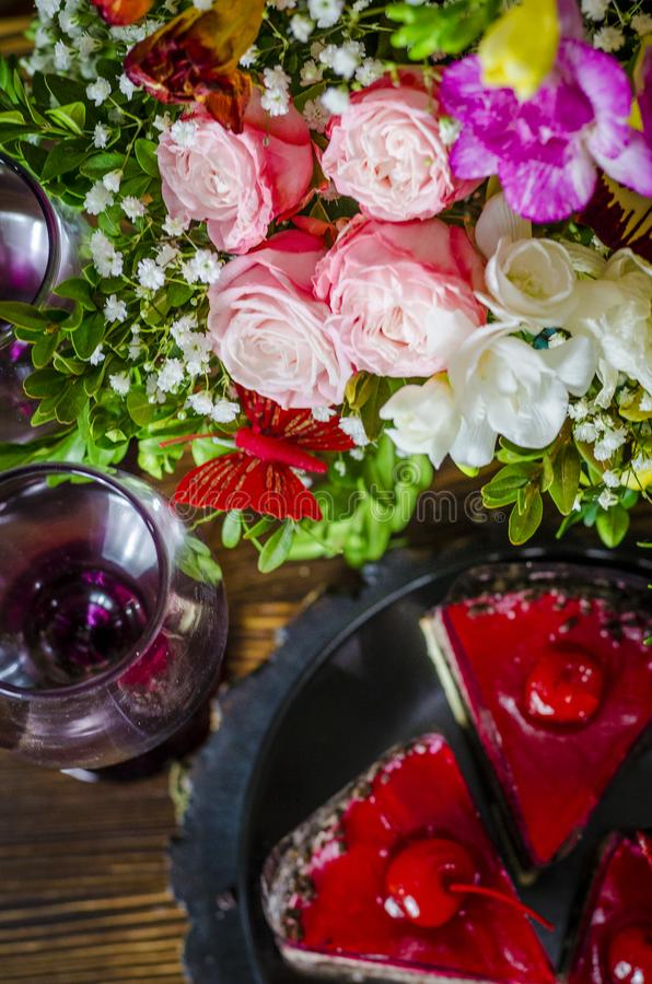 Cake with cherry. Birthday cake with cherry on a background of flowers stock photos