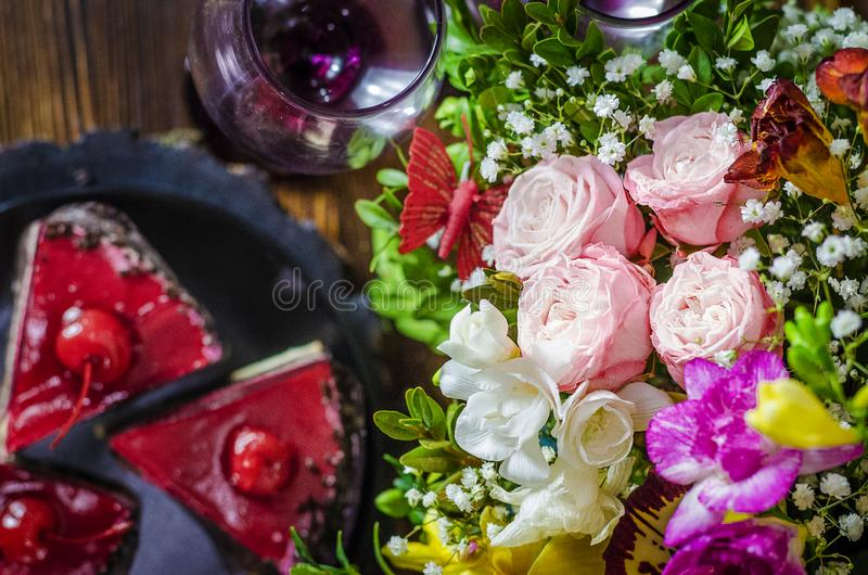 Cake with cherry. Birthday cake with cherry on a background of flowers royalty free stock photos