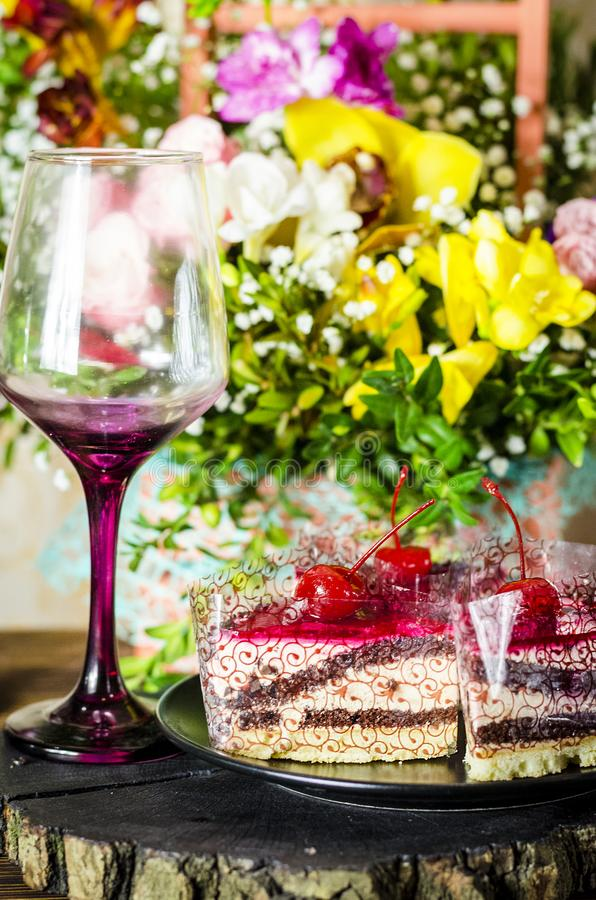 Cake with cherry. Birthday cake with cherry on a background of flowers royalty free stock images