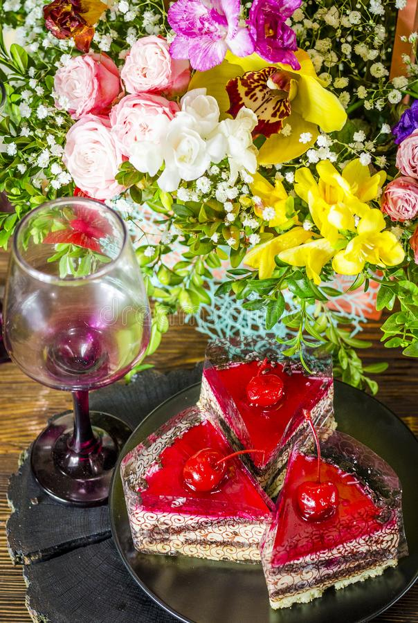 Cake with cherry. Birthday cake with cherry on a background of flowers stock image