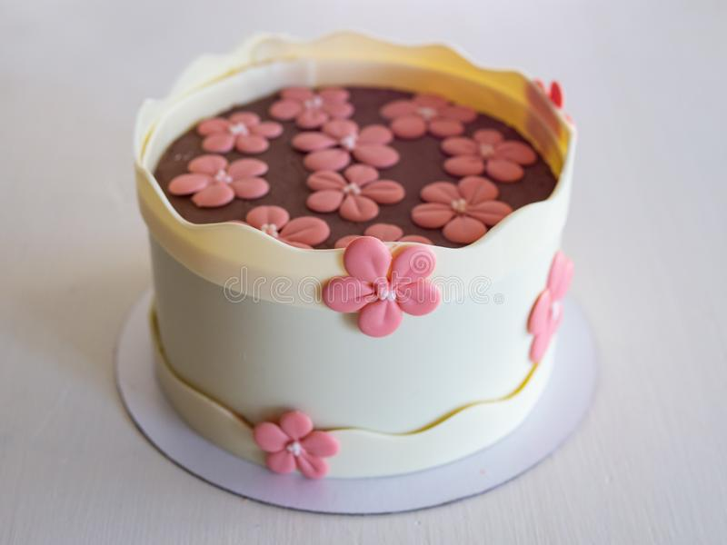 Cake with a chocolate decor - chocolate white boards and pink chocolate flowers. Cake for birthday, anniversary and any other stock image