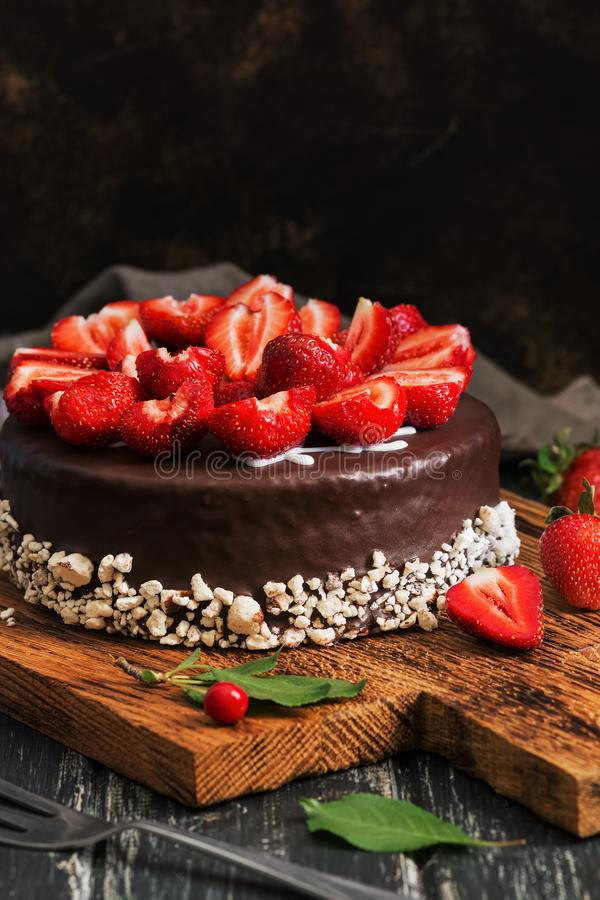 Cake in chocolate glaze with fresh strawberries on a dark old wood plank background. Selective focus stock photo