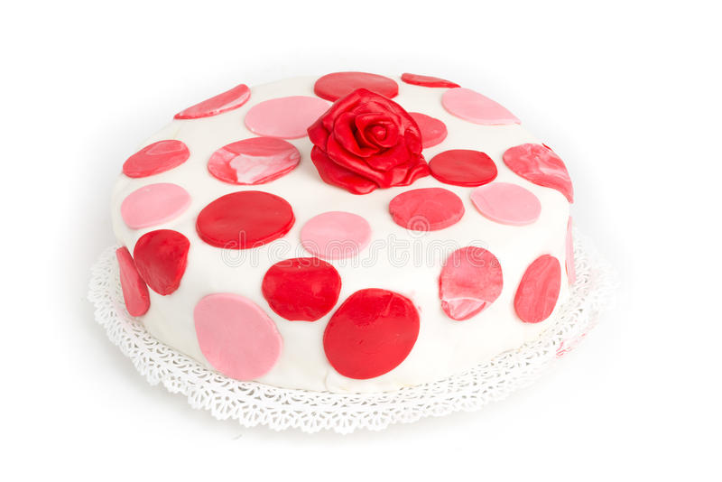Cake covered with sugar paste with red dots presented on a tray on the table. Cake covered with sugar paste with red dots presented on a tray isolated on a white stock images