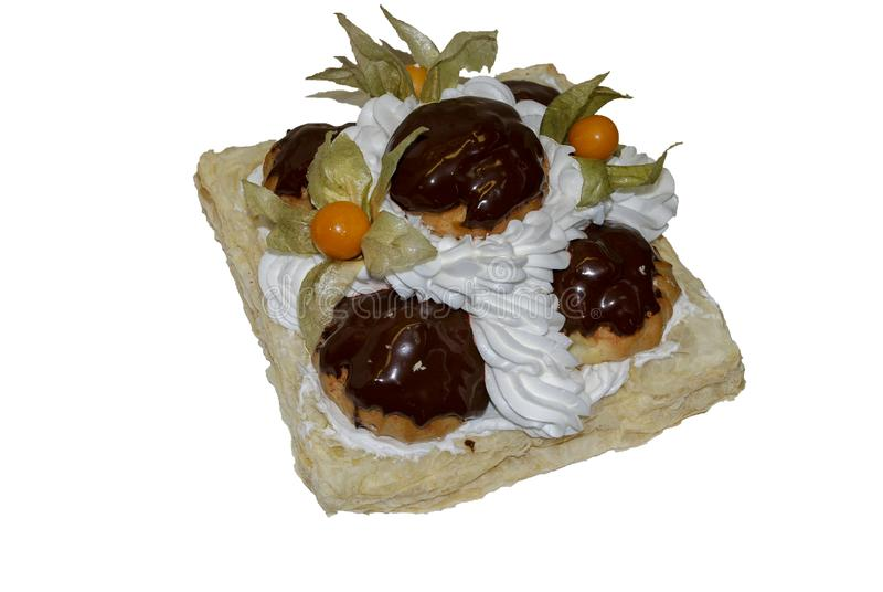Cake decorated with profiteroles with chocolate, physalis royalty free stock image