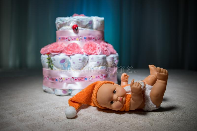 Cake of diapers, baby shower gift diaper, wrapped diapers, a roll of diapers, wrapped a clean diaper on table with baby doll decor stock photo