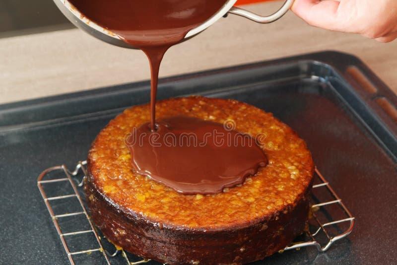 Cake die met vloeibare chocolade in lagen aanbrengen stock foto's