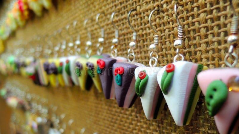 Cake Earrings. Table full of cake-like colourful earrings stock photo