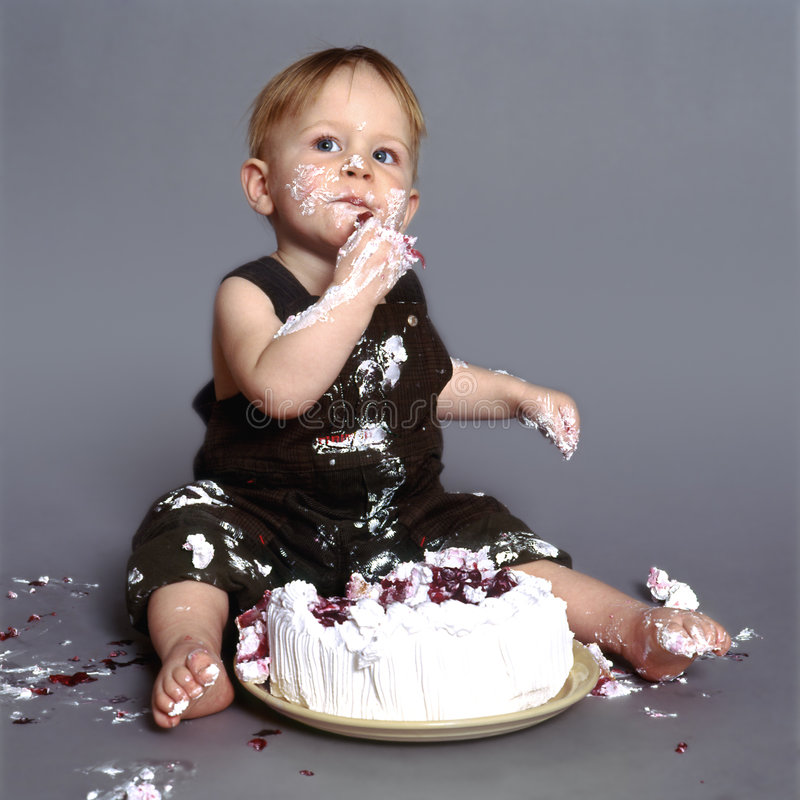 Cake eater. Cute little boy eating his first birthday cake stock photo