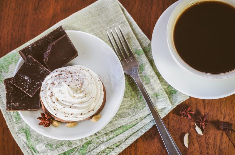 A cake with egg white cream, pieces of chocolate, anise, cardamom and fork on a green serviette and a cup of hot coffee. On a wooden table stock photo