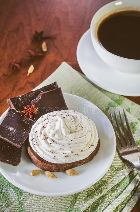 A cake with egg white cream, pieces of chocolate, anise, cardamom on a green serviette and a cup of hot coffee. On a wooden table stock image