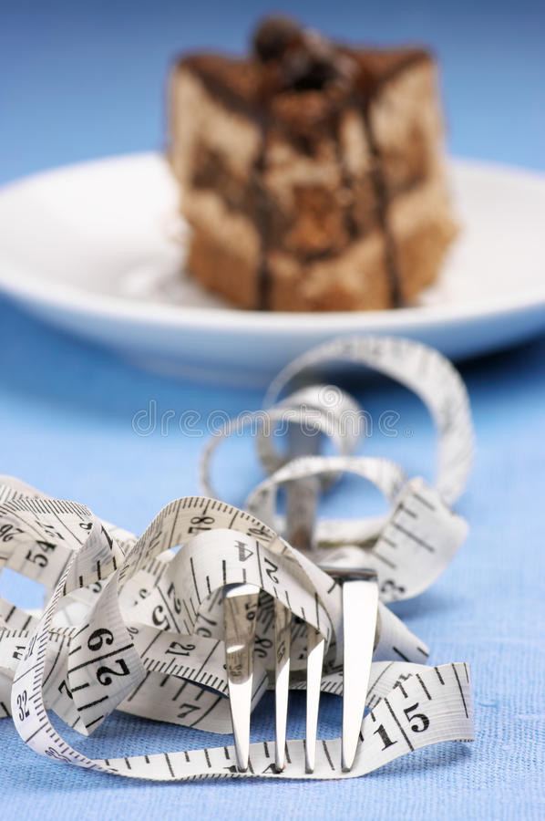 Cake and fork in measuring tape royalty free stock images
