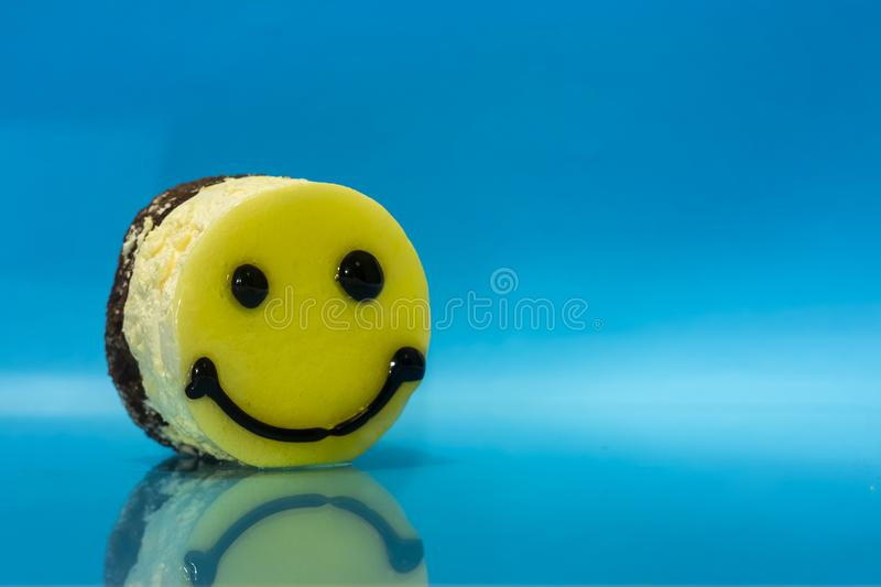 Cake in the form of an emoticon. On a blue background stock images