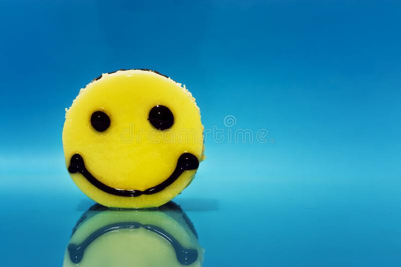 Cake in the form of an emoticon. On a blue background royalty free stock photography