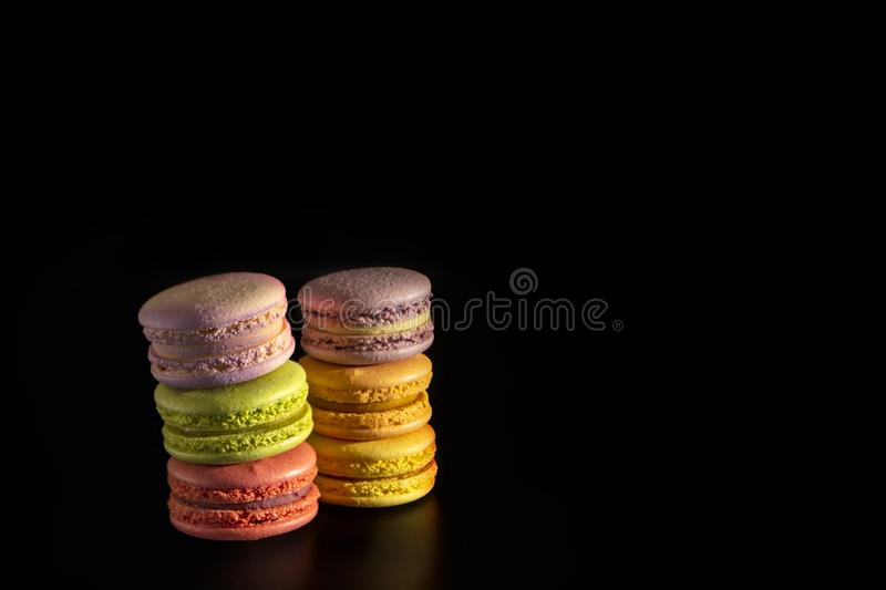 Cake french macaroons, sweet colorful macarons stand on each other on a black background stock image