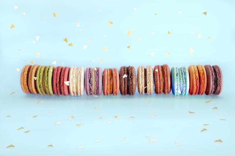 Cake french macaroons, sweet colorful macarons stand in row and gold confetti on light blue background. Birthday holiday party. Concept. Trendy pattern for royalty free stock photos