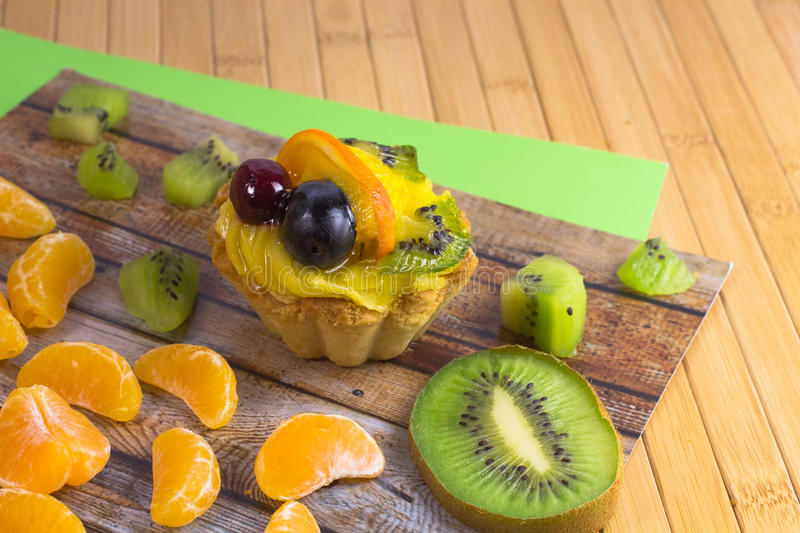 Cake with fruits. Kiwi and tangerine slices on table. Cake with fruits. Kiwi and tangerine slices on a table royalty free stock images