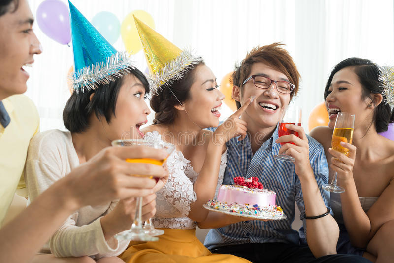 Cake fun. Friends having fun with cake at party royalty free stock images