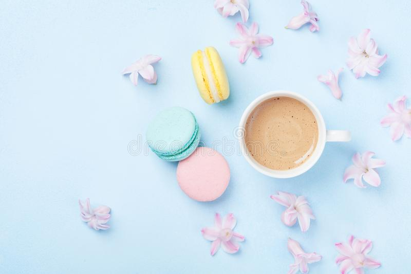 Cake macaron or macaroon, pink flowers and coffee on blue pastel background top view. Creative and fashion composition. Flat lay. Cake macaron or macaroon, pink stock photography