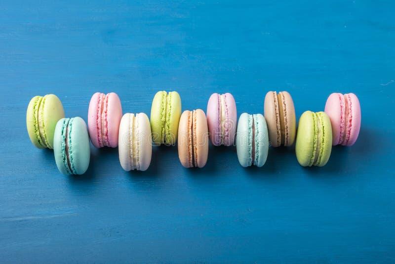 Cake macaron of makaron op blauwe achtergrond van hierboven, kleurrijke amandelkoekjes, pastelkleuren, uitstekende kaart, hoogste stock foto
