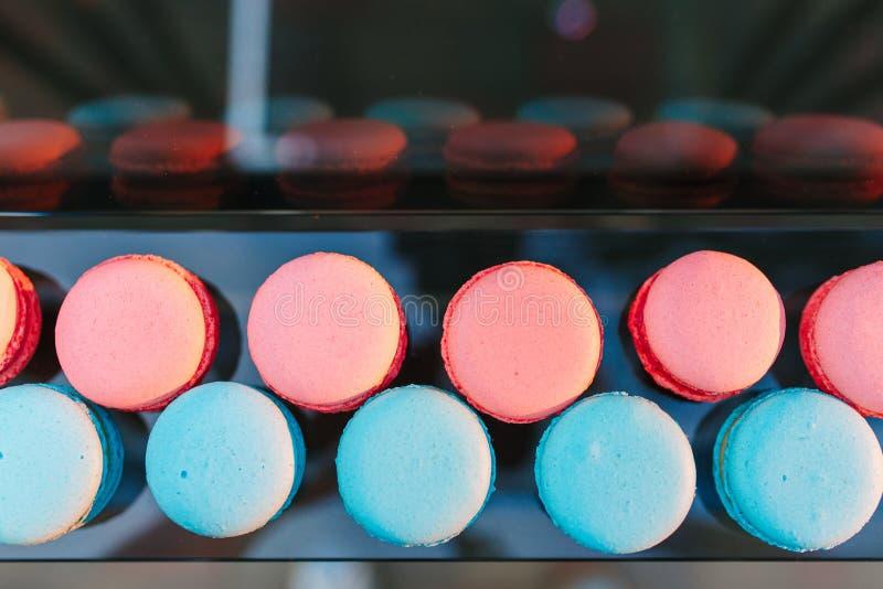 Cake macaron of makaron op glas hoogste mening als achtergrond, kleurrijke amandelkoekjes, pastelkleur het rode en blauwe kleuren stock foto