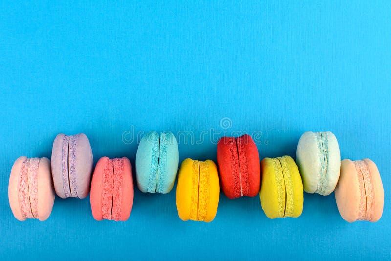 Cake macaron of makaron op turkooise achtergrond van hierboven, kleurrijke amandelkoekjes, pastelkleuren, uitstekende kaart, bove stock afbeelding