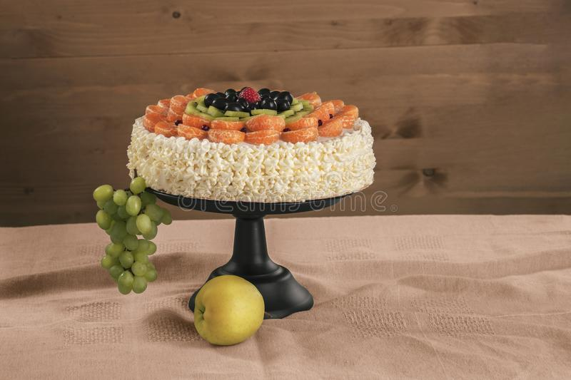 Cake made from natural ingredients, fresh kiwi fruit, grapes, tangerine and strawberries is on a stand on the table stock image