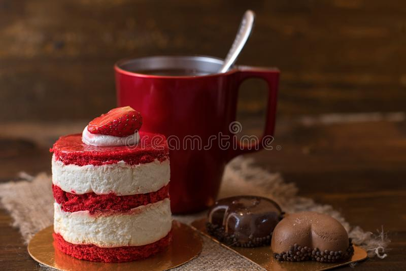 Cake met aardbeien, koekjes en een Rode Kop van koffie op een houten lijst stock foto's