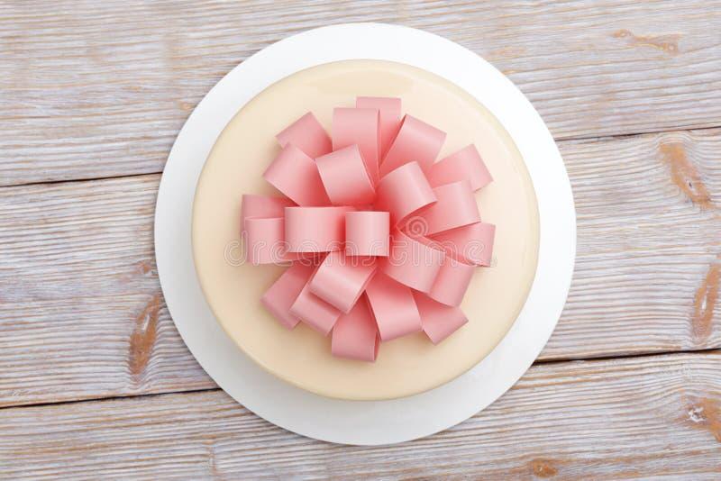 Cake met chocoladeboog op een houten hoogste mening als achtergrond stock afbeelding