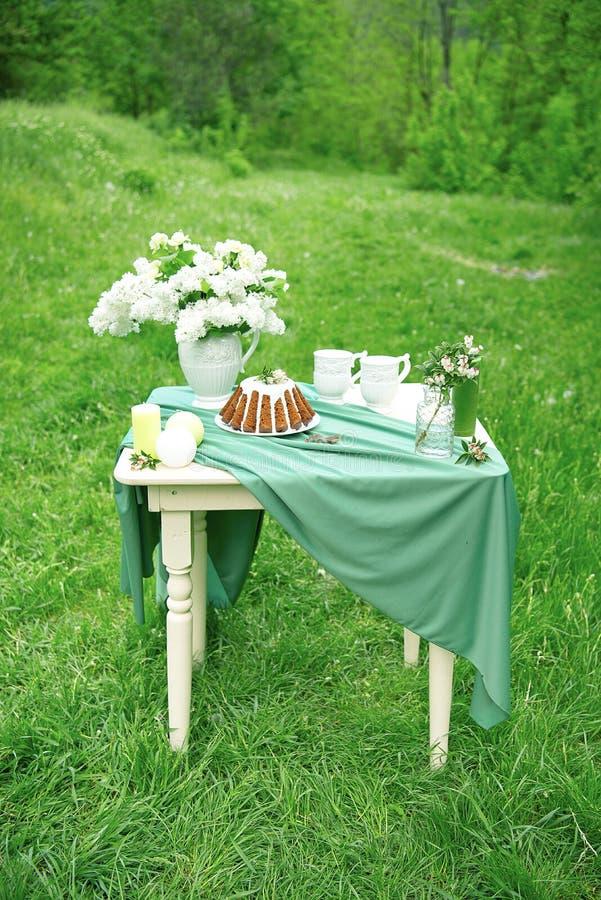 Cake met sommige die koppen op picknicklijst met bloemen, kaarsen, vaas op groen gebied wordt verfraaid royalty-vrije stock foto
